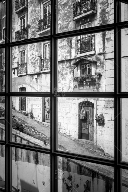 Lisbon, Portugal - April 15, 2014: View through window of hilly street with historic building