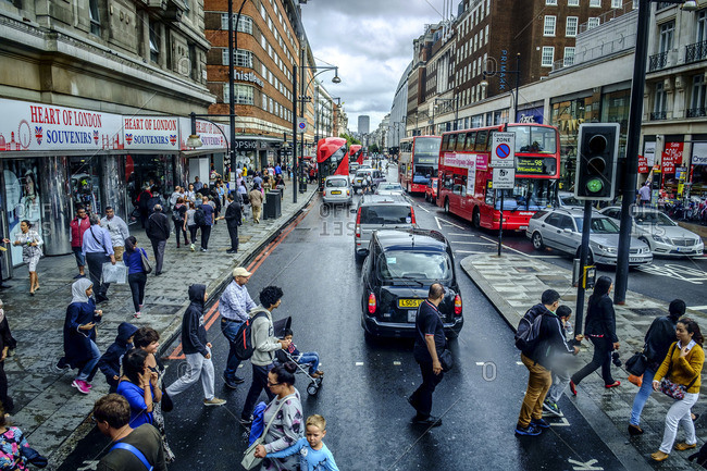 London, England - September 10, 2014: Busy street crossing with traffic and pedestrians