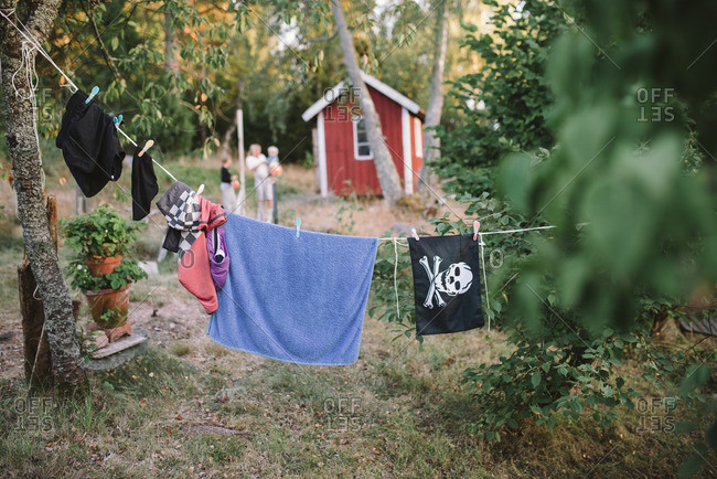 Towels and a pirate flag hanging on a clothesline in the woods