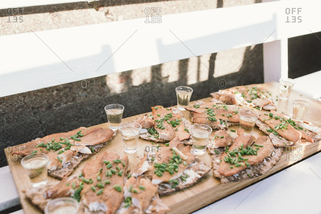 Fish filets on a wooden serving board with green onions and shot glasses