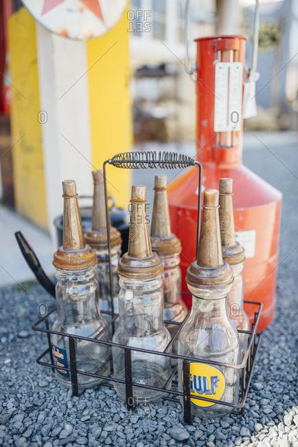 Antique motor oil bottles in a wire basket