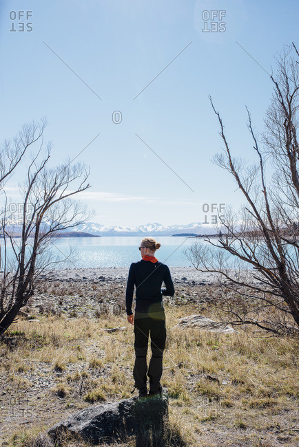 Man standing on a rock looking out over a lake and distant mountains