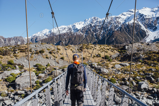 Young man crossing a pedestrian bridge on a hike in the mountains
