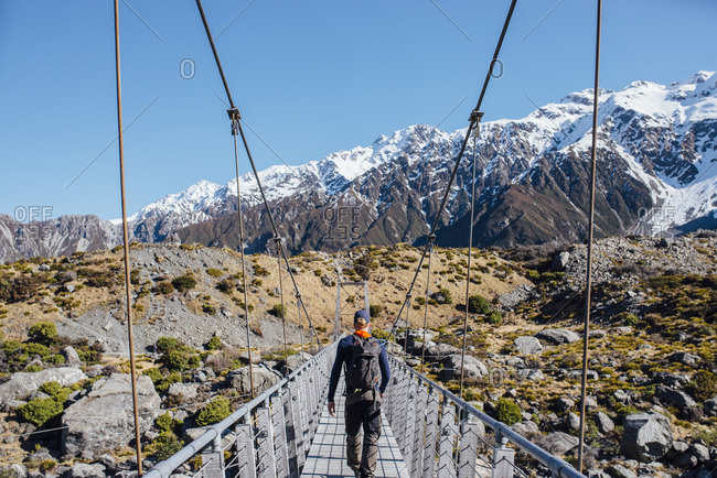 Young man walking across a pedestrian bridge on a mountain hike