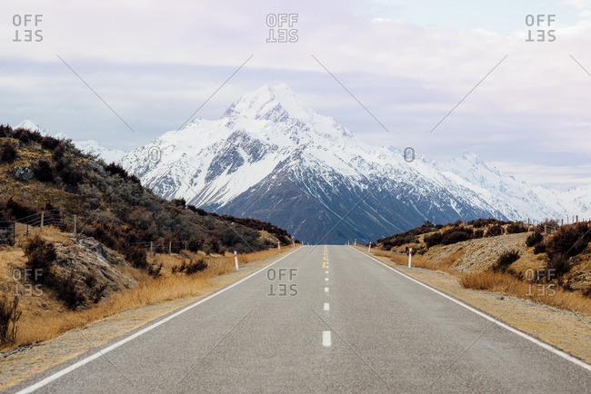 Distant mountain seen from an empty highway between hills