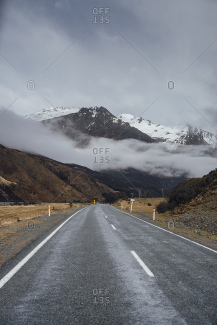 Empty highway and distant mountains in fog