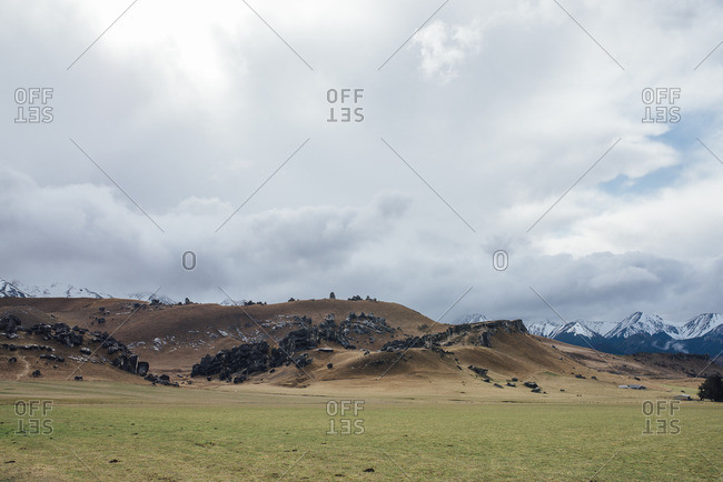 Black boulders on a grassy hillside in mountains