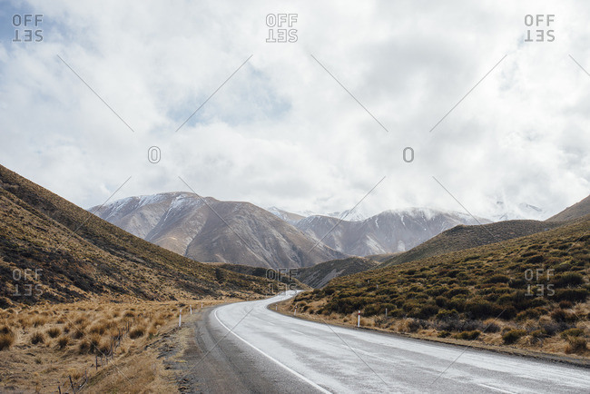 Highway winding through mountains and dried grasses