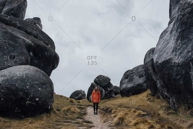 Woman standing on a path between large black boulders