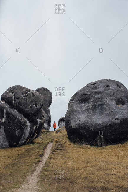 Woman walking on a hillside path between large boulders