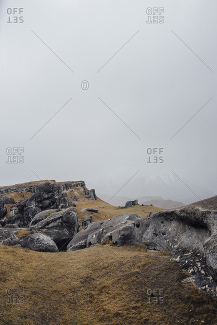 Black boulders on a grassy mountain hillside in the fog