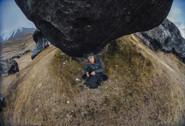 Young backpacker sitting below a black boulder on a grassy hillside