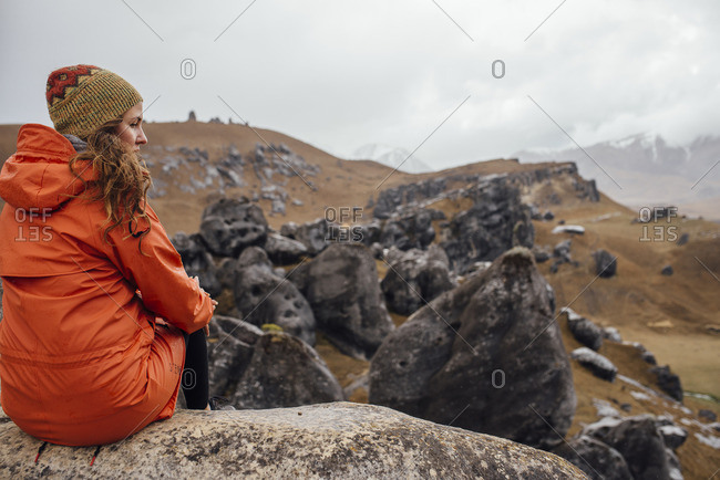 Woman sitting and overlooking a field of boulders on a grassy hill