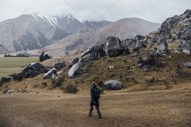 Backpacker walking across a field near a hill of massive boulders