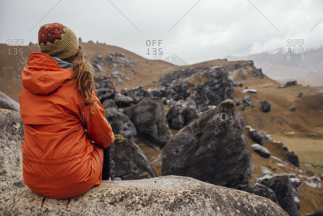 Hiker sitting and overlooking a field of boulders on a grassy hill