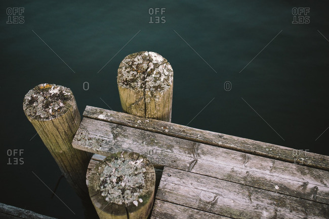 Wooden posts at the corner of a dock on a lake