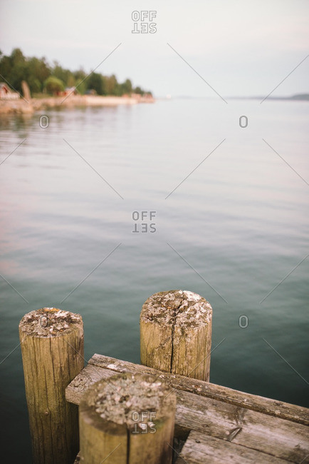 Three wooden posts at the corner of a dock on a lake
