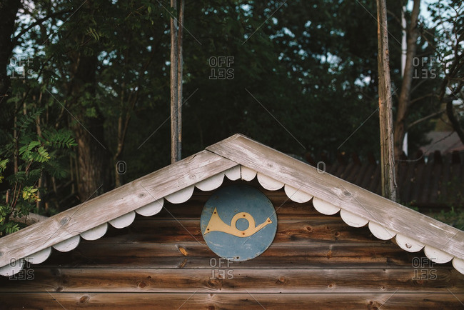 Medallion with a bugle near the roof of a rustic cabin