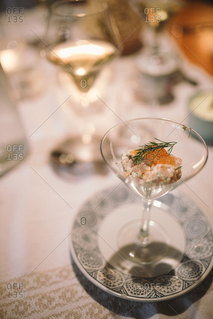 Salad in a martini glass garnished with orange and dill