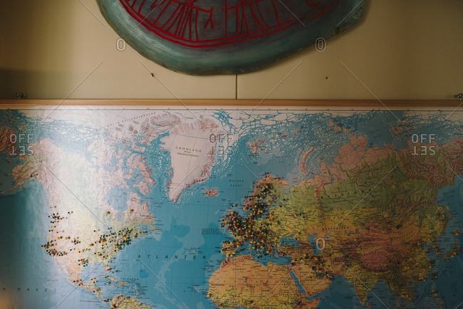 World map hung on a wall with pins on various locations