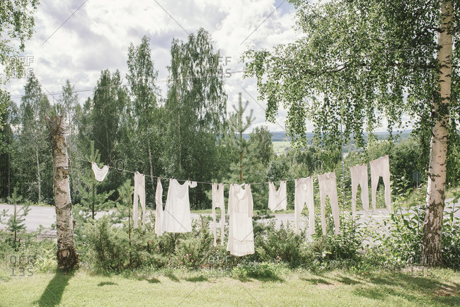 White linens hanging on a clothesline between two trees