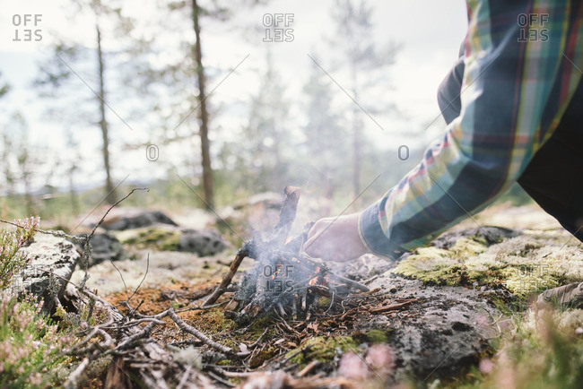 Hands of a young man building a campfire