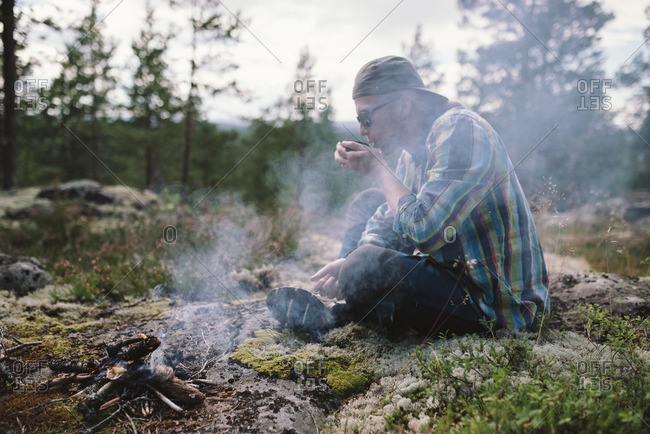 Young man blowing on kindling for a campfire in the woods