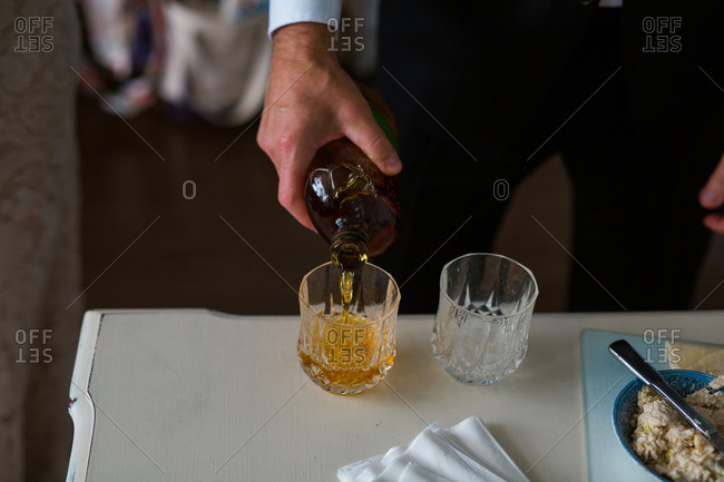 Groom pouring drink on his wedding day
