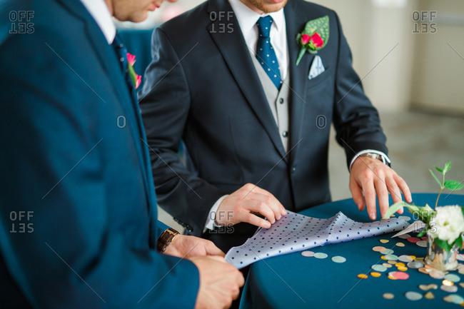 Men folding handkerchief into a pocket square
