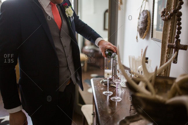 Groom pouring champagne on his wedding day