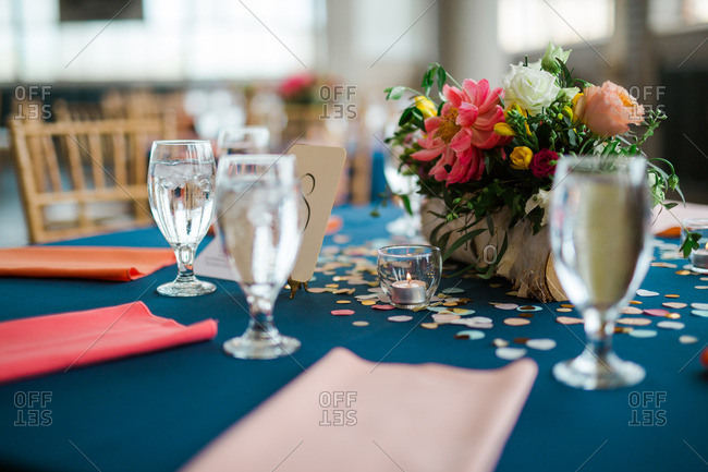 Table with glasses of water and floral centerpiece at a wedding reception