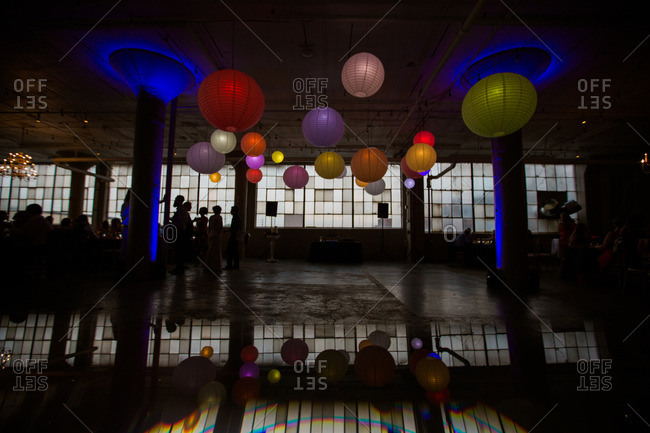 Colorful paper lanterns above dance floor at a warehouse wedding reception