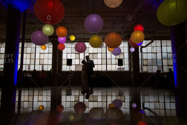 Bride and groom dance under colorful paper lanterns at their wedding reception