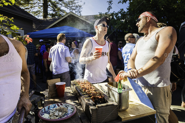 July 4, 2016: People gather at grill during a 4th of July block party celebration