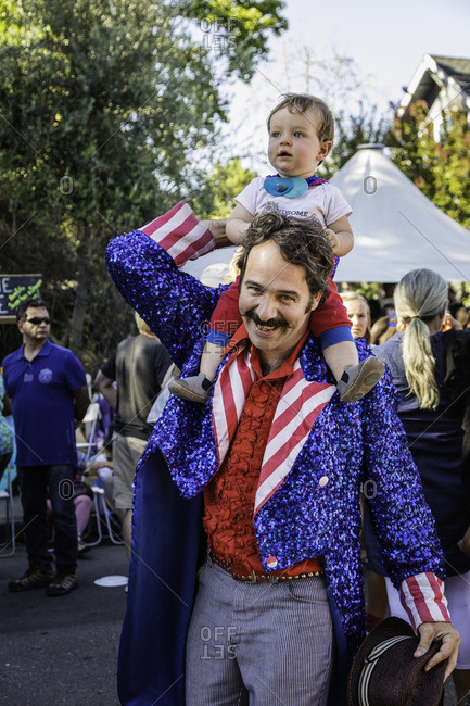 July 4, 2016: A father dressed for 4th of July holds his son on his shoulders during a block party celebration
