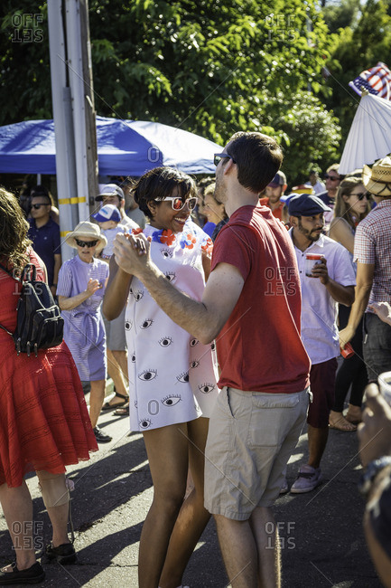 July 4, 2016: A young couple dance together in the street during a block party celebration
