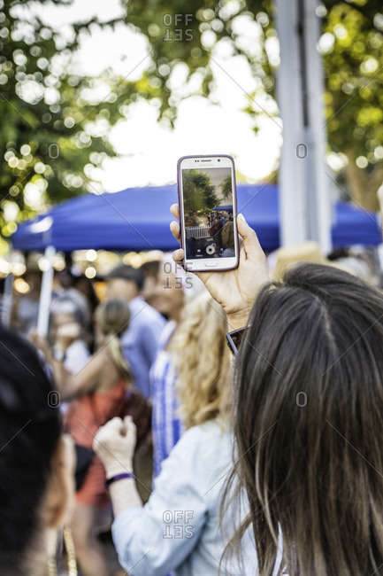 July 4, 2016: A young woman takes video at street festival on her smartphone
