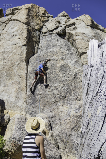 Sierra Nevada, California - July 16, 2016: Man in hat watches rock climber on vertical granite wall
