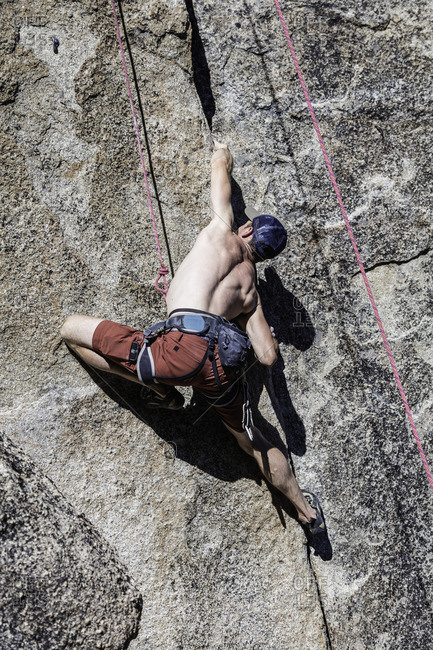 Sierra Nevada, California - July 16, 2016: Shirtless climber finds a handhold in crack of rock face