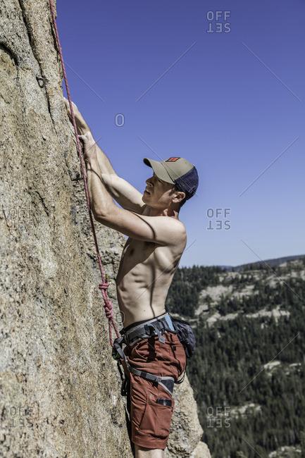 Sierra Nevada, California - July 16, 2016: Side view of rock climber on a vertical granite wall in Sierra Nevada's, California