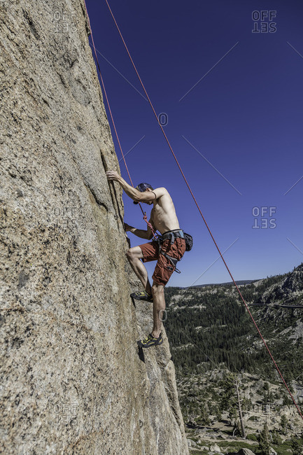 Sierra Nevada, California - July 16, 2016: Roped climber makes his way up a vertical rock face