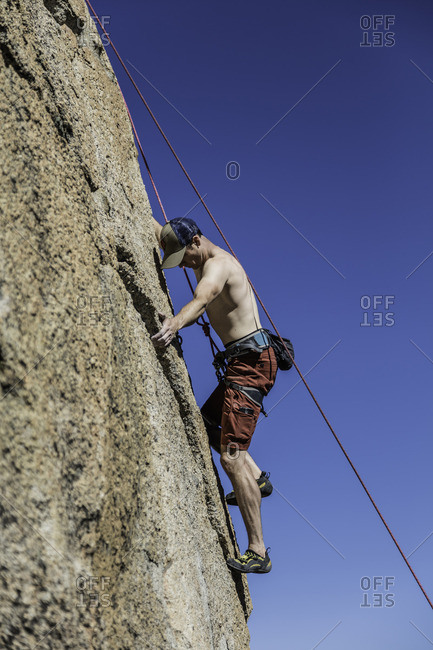 Sierra Nevada, California - July 16, 2016: Rock climber clings to ridge in rock face while ascending cliff
