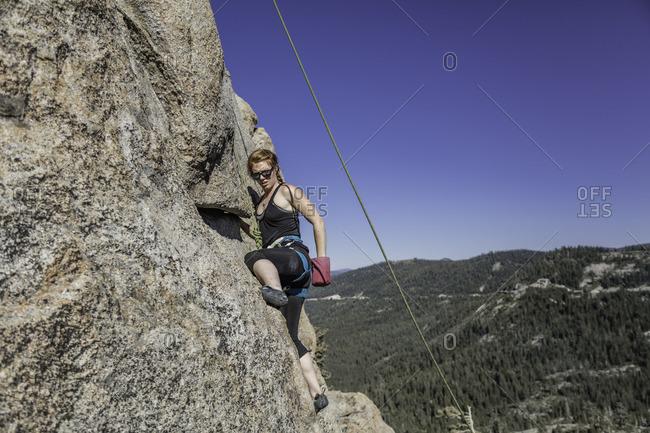 Sierra Nevada, California - July 16, 2016: Woman climbing up a steep rock face in the Sierra Nevada's, California