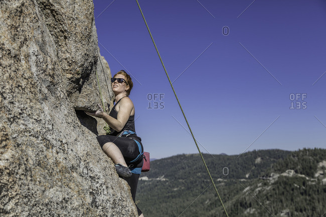 Sierra Nevada, California - July 16, 2016: Climber holds onto underside of small outcropping during her climb