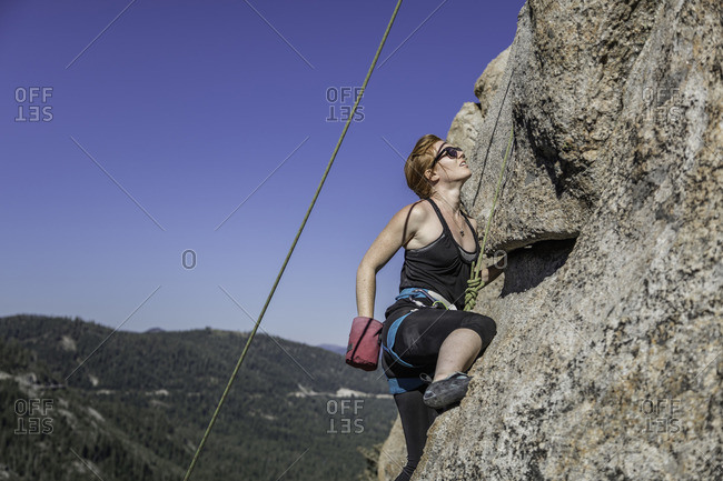 Sierra Nevada, California - July 16, 2016: Climber reaches into her chalk back during ascent up rock face