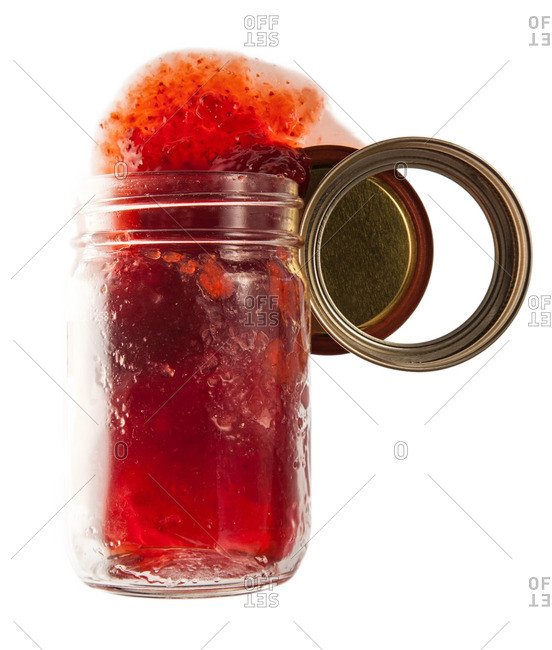 Glass jar with strawberry jelly spilling out