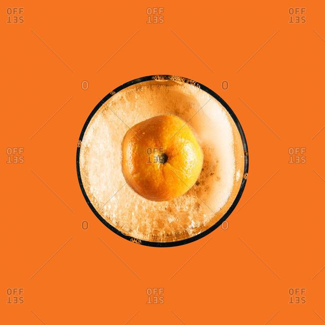 Orange fruit floating in bubbles on orange background
