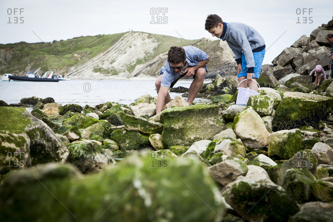 Father and teenaged son exploring rocks on beach