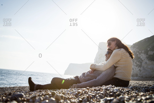 Woman holding her partner as they relax on beach