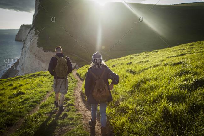 Couple walk on hiking trail above coastal cliffs